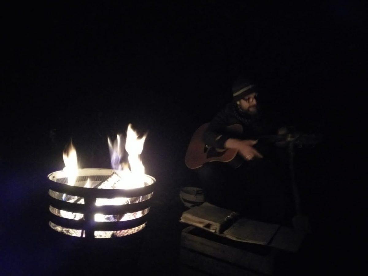 Martin Gitarre spielend am Lagerfeuer