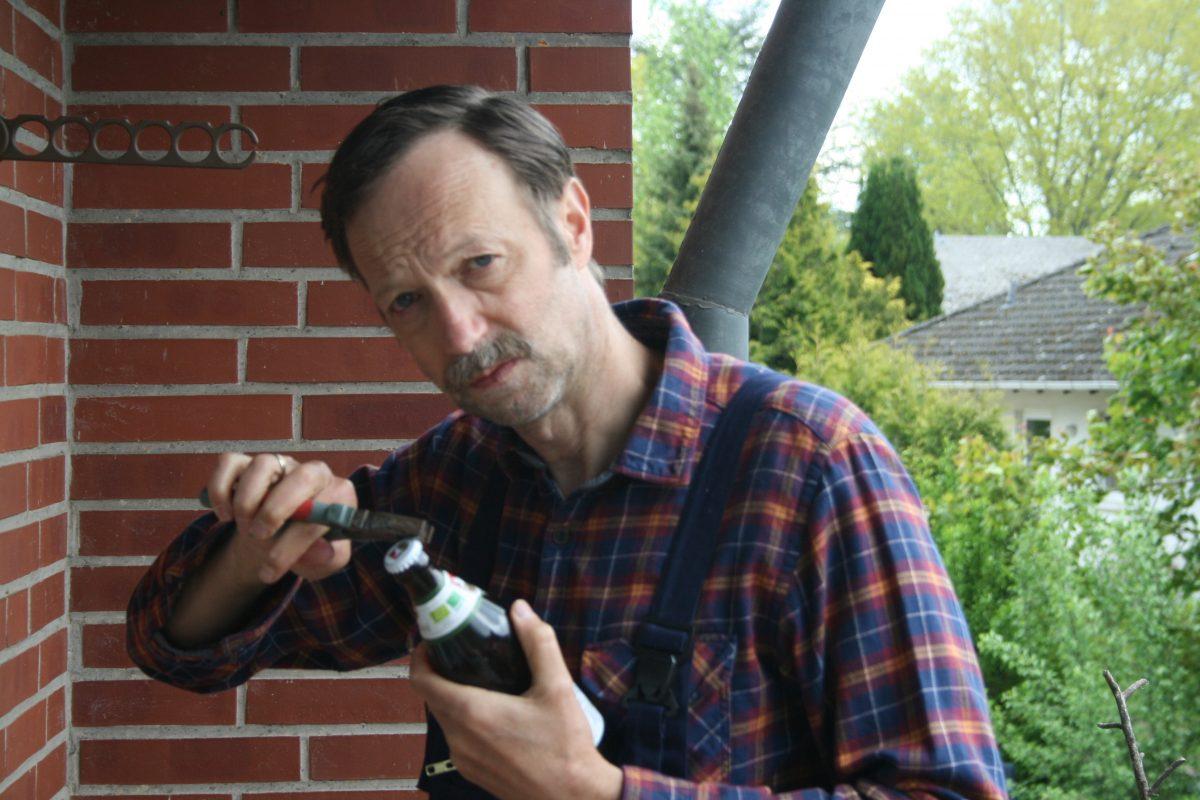 Martin in Handwerkerkluft mit Schnauzbart öffnet ein Bier