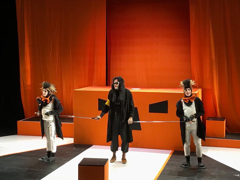 Drei Pinguine und ein Maulwurf in orangefarbenem Bühnenbild